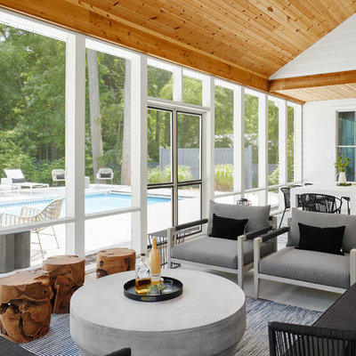 This is an example of a coastal concrete screened-in back porch design in Chicago with a roof extension.