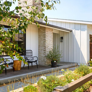 Country front porch idea in Orange County with a roof extension