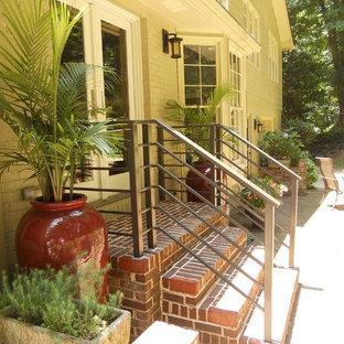 Ispirazione per un piccolo portico tradizionale dietro casa con un giardino in vaso, pavimentazioni in mattoni e un tetto a sbalzo