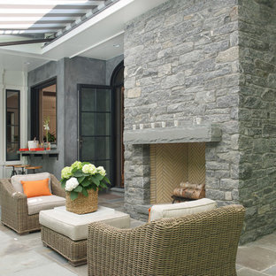 Inspiration for a large transitional stone back porch remodel in New York with a fire pit and an awning