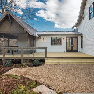 Diseño de porche cerrado de estilo de casa de campo, de tamaño medio, en patio lateral y anexo de casas, con entablado