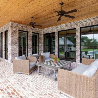 Ispirazione per un grande patio o portico country dietro casa con pavimentazioni in mattoni e un tetto a sbalzo