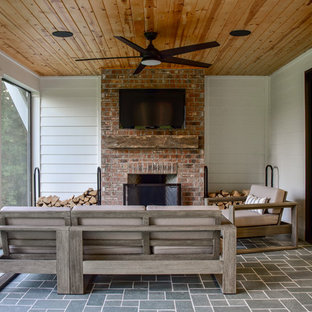 This is an example of a mid-sized country stone back porch design in Other with a fireplace and a roof extension.