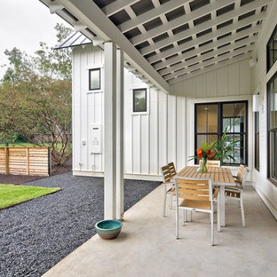 Farmhouse concrete porch photo in Austin with a roof extension