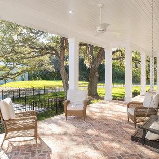 Foto di un portico country davanti casa con pavimentazioni in mattoni e un tetto a sbalzo
