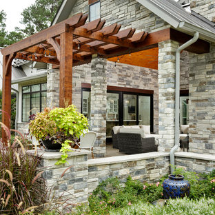 Esempio di un portico country di medie dimensioni e davanti casa con un caminetto, pavimentazioni in cemento e una pergola