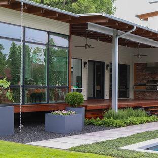 Esempio di un grande portico moderno nel cortile laterale con lastre di cemento e un tetto a sbalzo