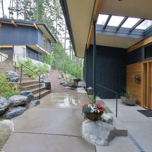 This is an example of a contemporary concrete porch design in Seattle with a roof extension.