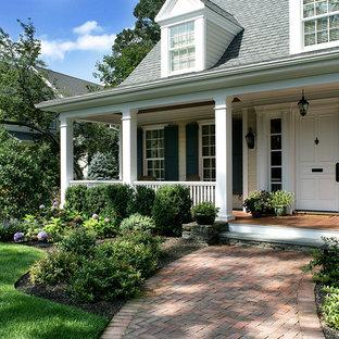 Imagen de terraza clásica, en patio delantero y anexo de casas, con entablado