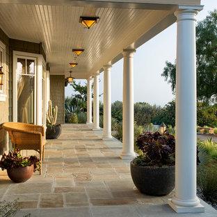 Immagine di un portico vittoriano davanti casa con pavimentazioni in pietra naturale, un tetto a sbalzo e un giardino in vaso