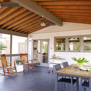 Diseño de porche cerrado tradicional renovado, en anexo de casas, con suelo de baldosas