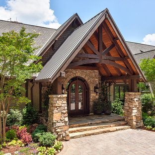 Large mountain style stone front porch photo in Other with a roof extension