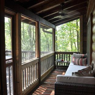 Inredning av en rustik liten innätad veranda, med takförlängning och trädäck
