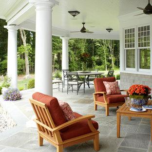 Idee per un grande portico vittoriano dietro casa con un tetto a sbalzo e pavimentazioni in pietra naturale