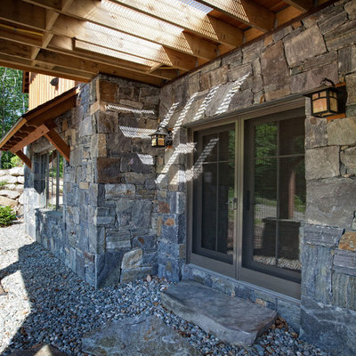 Mid-sized mountain style stone back porch photo in Burlington with a pergola