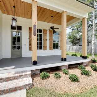 Mid-sized country front porch idea in New Orleans with decking and a roof extension