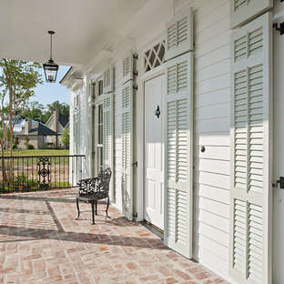 Inspiration for a timeless brick porch remodel in New Orleans with a roof extension