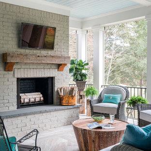 Imagen de terraza tradicional renovada, grande, en patio trasero y anexo de casas, con chimenea y suelo de baldosas