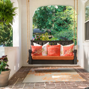 Mid-sized tuscan brick porch idea in Other with a roof extension