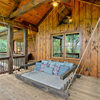 This is an example of a mid-sized rustic front porch design in Other with a roof extension.