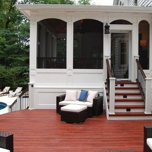 Ispirazione per un grande patio o portico chic dietro casa con un portico chiuso, pedane e un tetto a sbalzo