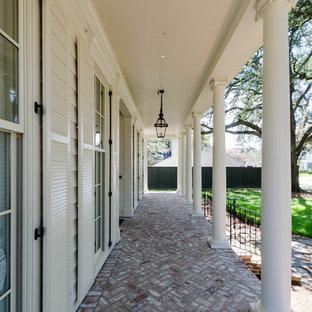 Idee per un grande portico vittoriano davanti casa con pavimentazioni in mattoni e un tetto a sbalzo