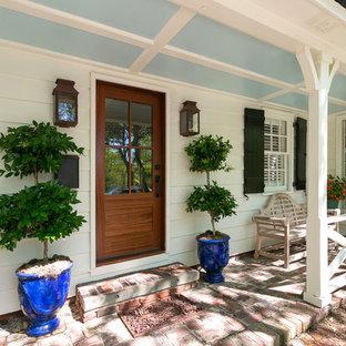 Immagine di un portico classico davanti casa con pavimentazioni in mattoni e un tetto a sbalzo