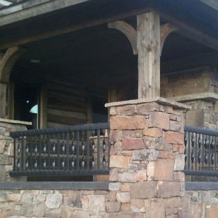Large mountain style stone side porch idea in Other with a fire pit and a roof extension