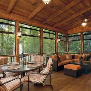 Ejemplo de porche cerrado clásico renovado, grande, en patio trasero y anexo de casas, con entablado