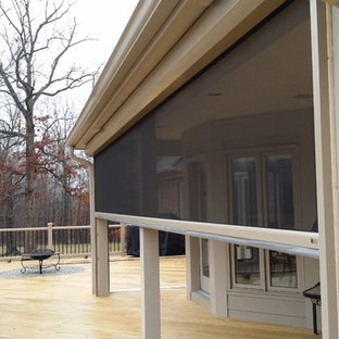 This is an example of a large craftsman screened-in back porch design in Louisville with a roof extension and decking.
