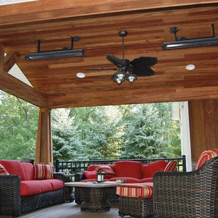 This is an example of a mid-sized craftsman back porch design in New York with a roof extension.