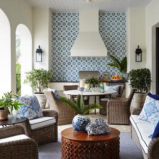 Modelo de terraza tropical, extra grande, en patio trasero y anexo de casas, con cocina exterior y adoquines de ladrillo
