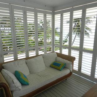 Foto de porche cerrado exótico, pequeño, en patio trasero y anexo de casas, con entablado