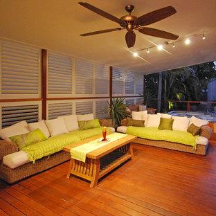 Esempio di un portico tropicale dietro casa con pedane e un tetto a sbalzo
