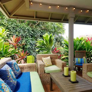 Esempio di un grande portico tropicale nel cortile laterale con pedane e un tetto a sbalzo