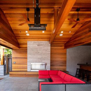 Esempio di un patio o portico industriale di medie dimensioni e dietro casa con un caminetto, lastre di cemento e un tetto a sbalzo