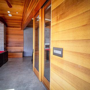 Idee per un portico industriale di medie dimensioni e dietro casa con un caminetto, lastre di cemento e un tetto a sbalzo