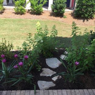 Immagine di un piccolo portico design davanti casa con un giardino in vaso, pavimentazioni in mattoni e un tetto a sbalzo