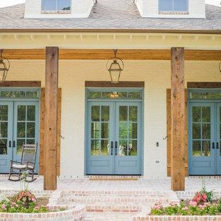 Immagine di un grande portico chic davanti casa con pavimentazioni in mattoni e un tetto a sbalzo