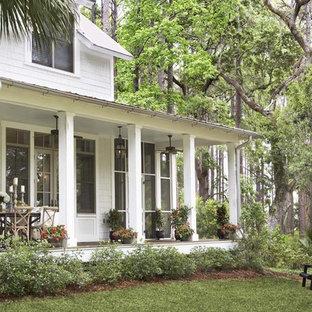 Immagine di un grande portico classico dietro casa con un giardino in vaso e un tetto a sbalzo