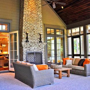Ispirazione per un portico chic di medie dimensioni e dietro casa con un focolare, un tetto a sbalzo e lastre di cemento