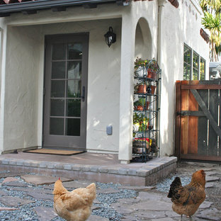 This is an example of a small mediterranean stone porch design in San Francisco with a roof extension.