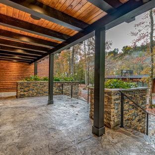Idéer för en stor rustik veranda framför huset, med utekrukor, stämplad betong och takförlängning
