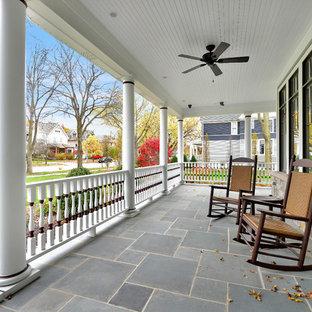 Ispirazione per un grande portico vittoriano davanti casa con un tetto a sbalzo e piastrelle