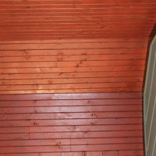 Immagine di un grande portico stile americano dietro casa con un portico chiuso, pedane e un tetto a sbalzo