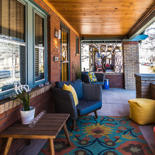 Small arts and crafts concrete front porch photo in Denver with a roof extension