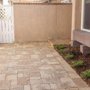 This is an example of a mid-sized mediterranean stone side porch design in Orange County.
