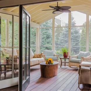 This is an example of a mid-sized traditional backyard screened-in verandah in Boston with decking and a roof extension.