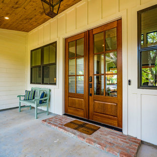 Inspiration for a mid-sized farmhouse concrete front porch remodel in Austin with a roof extension