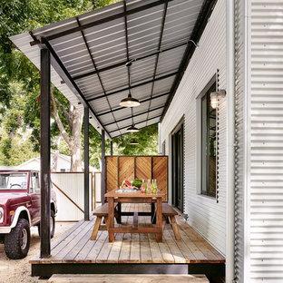 Immagine di un portico country nel cortile laterale con pedane e un parasole